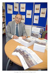 The author, Geoffrey Ball, signing books at the launch.